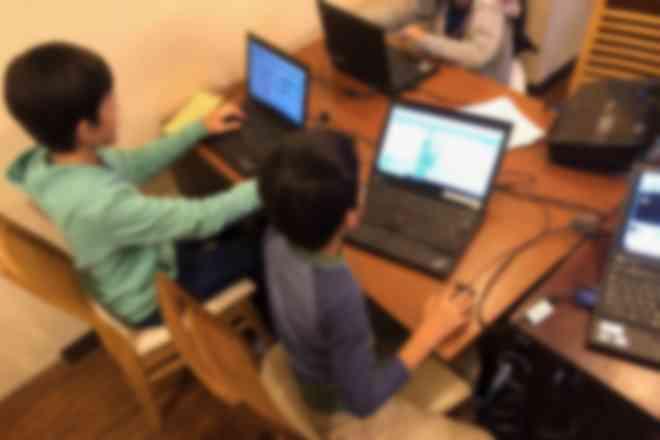 小学生がグループでプログラミングレッスンを受けている様子