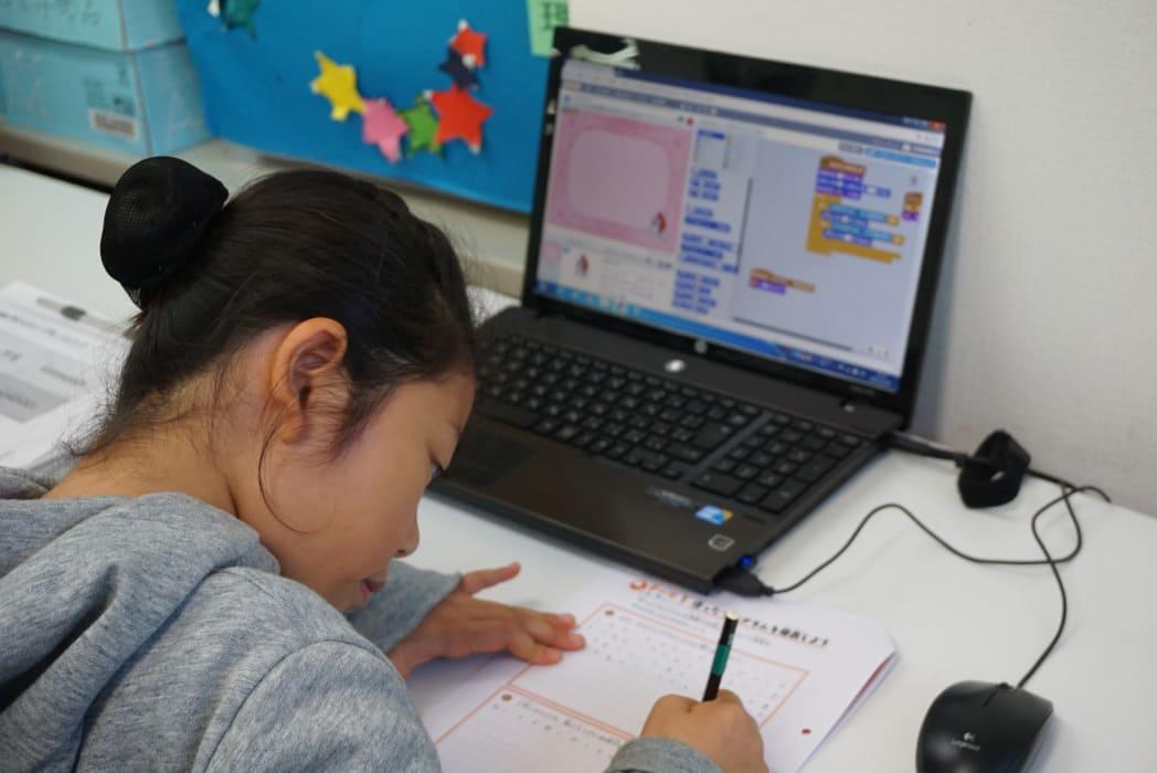 ヒューマンアカデミーアフタースクールの授業風景 制作物の発表のために作文を書く生徒